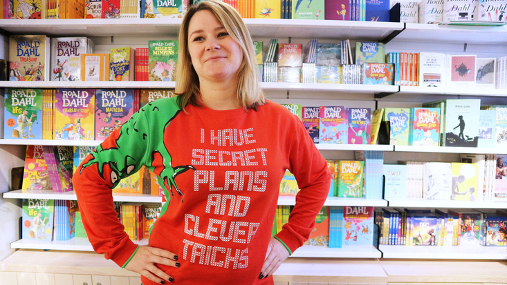 A lady wearing a jumper with the slogan 'I have secret plans and clever tricks'
