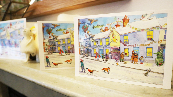 Christmas cards, featuring a snowy scene of the Roald Dahl Museum, sat on a mantelpiece