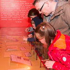 Family looking at archive case in Museum