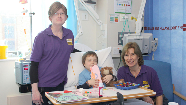 Two Roald Dahl storytellers with boy in hospital bed